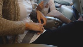 Close-up shot of female hands fastening seatbelt during airplane flight going to vacation with family, safety concept. Woman learning and obeying aviation stock video footage