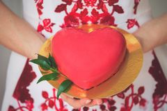 Close up shot of female hands holding golden plate with tasty festive cake shaped like a big red heart. Christmas, new year, birthday, valentine day concept stock image