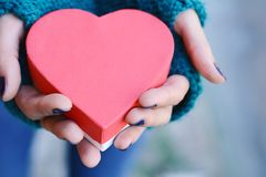 Female hands holding heart shaped gift box. Close up shot of female hands holding heart shaped gift box. Valentines day, romance concept stock image