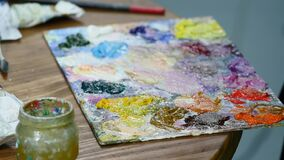 Close-up shot of female hands squeezing out a tube of paint onto the palette.  stock video