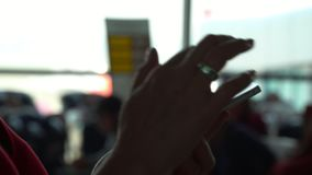 Close-up shot of female hands texting in messenger or typing sms on smart phone by the airport window. Boarding plane in. On this video you can see as the woman stock video footage