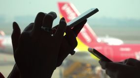 Close-up shot of female hands texting in messenger or typing sms on smart phone by the airport window. A silhouette of. On this video you can see as the woman stock footage