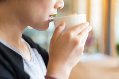 Close up shot of female youngster drink coffee and feeling relax. And cross process and soft flare filter Royalty Free Stock Images