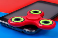 Close-up shot of fidget spinner lying on smartphone. Two-tone background stock images