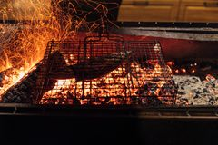 Fish in grill bar cooking on bbq Royalty Free Stock Images