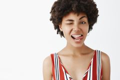 Close-up shot of flirty emotive and playful african american with afro hairstyle sticking out tongue and winking. Mysteriously using feminine seduction over stock photo