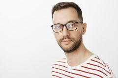 Close-up shot of focused smart attractive guy in black glasses, gazing at camera indifferently, standing over gray stock images