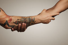 Close up shot of a forearm handshake. Close up of a forearm Roman, Civil war handshake of two young men, one with tattoos, on white background stock photography
