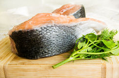 Close up shot of fresh salmon fish with parsley and dill on a wooden board Stock Photo