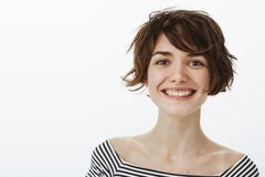 Close-up shot of friendly optimistic and happy european female coworker with stylish short haistyle, smiling joyfully. And gazing at camera with pleased and royalty free stock photography