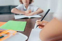 close-up shot of girl writing in notebook and boy Stock Image