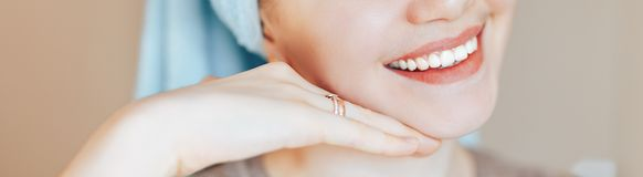 Close up shot of glad satisfied woman being happy after spa procedure, has fresh soft healthy skin, broad smile, white perfect. Teeth touch her face look at royalty free stock photo