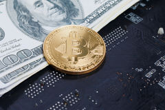 Close up shot gold Bitcoin on dollar banknote over computer prin Stock Image