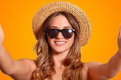 Close up shot of good looking female with friendly smile, wears trendy sunglasses and straw hat, makes selfie portrait on unrecogn stock images