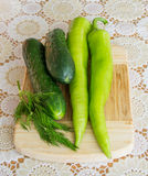 Close up shot of green pepperoni, dill and cucumbers on a wooden board Stock Photography