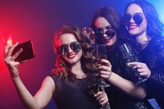 Close-up shot of group of laughing girls having party, take self. Ie with smartphone. Lifestyle concept Stock Photography
