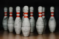 Close-up shot of grungy bowling pins in gate on black royalty free stock photo