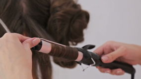 Close up shot. Hairdresser doing hairstyle for young pretty woman - making curls stock video footage