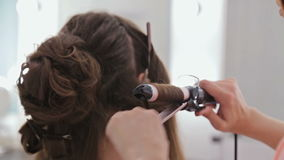 Close up shot. Hairdresser doing hairstyle for young pretty woman - making curls stock video