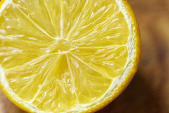 Close up shot of half a cut lemon. Close up macro photograph of a lemon that has been cut in half. The lemon is not fresh and is a few days old. The skin is dry stock image