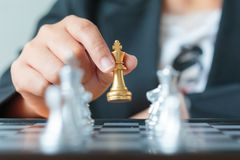 Close up shot hand of business woman holding golden chess betwee. N row of silver chess on white and black chess board for business challenge competition winner Royalty Free Stock Photography