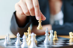 Close up shot hand of business woman moving golden chess to defe Stock Photo