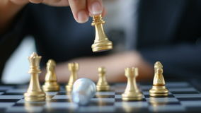 Close up shot hand of business woman moving golden chess to defeat a silver king chess on white and black chess board for business