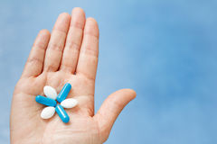 Close-up shot of hand holding blue and white pills in the form l. Ike flower. Pills on woman hand Royalty Free Stock Photography
