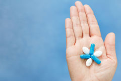 Close-up shot of hand holding blue and white pills in the form l. Ike flower. Pills on woman hand Royalty Free Stock Photo