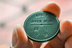 A close up shot of a hand holding a green token for the Hong Kong Star Ferry stock photo
