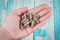 Close-up shot of a hand holding several capsuls pills. Close-up shot of a hand holding several pills Stock Photo