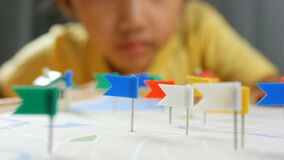 Close up shot hand of kids and mother pinning color pin at the map metaphor planning for transport and travel.  stock video
