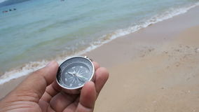 Close up shot hand of mand holding a compass on the sand beach with nature sea and wind ambient sound.  stock footage