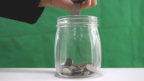 Close up shot hand of woman drop the coins to glass jar over green background stock video footage