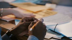 Close-up shot, hands of African American office worker holding pencil, stressed at team meeting discussion behind table. Close-up shot, hands of African stock footage