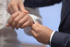 Young white Caucasian male being helped with his white shirt by another elegantly dressed man. Close up shot of hands of classy groom, stylish businessman, or Royalty Free Stock Photography