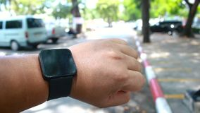 Close up shot hands of man using smart watch in nature public park with ambient sound.  stock footage