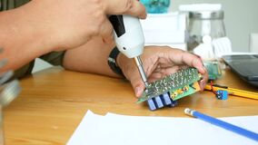 Close up shot hands of mechanic man using electric screwdriver to spin the screw on electronic print circuit board with ambient so. Und stock video