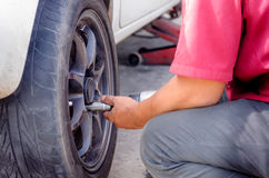 Close up shot of the hands of mechanics using pneumatic wrench t. O loosen the nut wheel of car royalty free stock photo