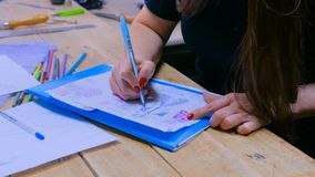 Fashion designer drawing design sketch. Close up shot - hands of professional tailor, designer drawing fashion sketch at atelier, studio. Dressmaking, creativity stock images