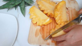 Close up shot hands of women using kitchen knife to cutting and peeling ripe pineapple shallow depth of field with ambient sound.  stock footage