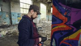 Close-up shot of handsome bearded man graffiti painter working inside adandoned building using earosol paint to create. Abstract image on old pillar. Creativity stock video