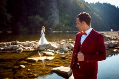 Close-up shot of the handsome groom in red suit looking over his shoulder at the charming bride standing far away on the royalty free stock image