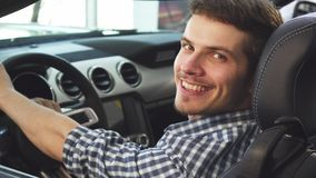 Close up shot of a handsome man sitting in his convertible, smiling joyfully stock image