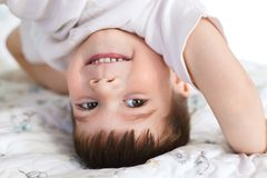 Close up shot of handsome smiling little boy stands on head, being glad, has fun after good sleep, has pleasant smile on face, has. Appealing appearance Royalty Free Stock Photos