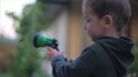 Close-up shot of a happy little boy watering flowers with a spray gun. The child smiles, the concept of children`s stock footage