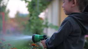 Close-up shot of a happy little boy watering flowers with a spray gun. The child smiles, the concept of children`s stock video