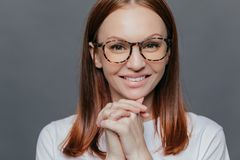 Close up shot of happy young European woman has pleasant smile, keeps hands together near chin, wears casual white clothes, royalty free stock images