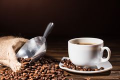 close-up shot heap of coffee beans cup and metal scoop on rustic royalty free stock photography