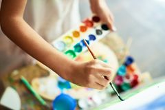 Drawing on Canvas. Close-up shot of highly gifted little artist drawing with watercolors on canvas, blurred background Stock Photo